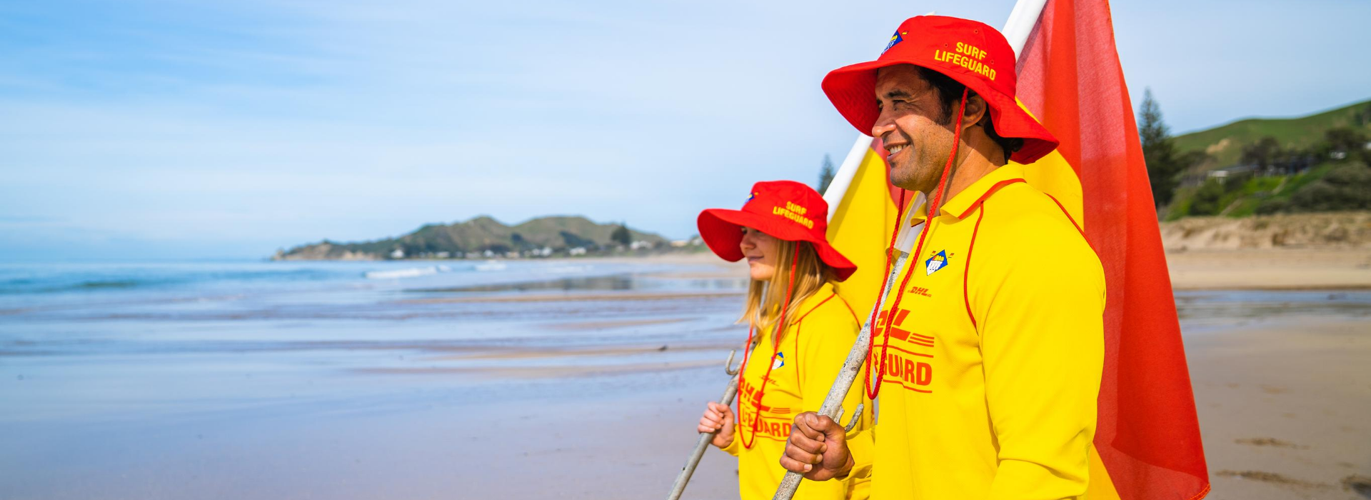 Female and male lifeguards with flags staring into distance side shot