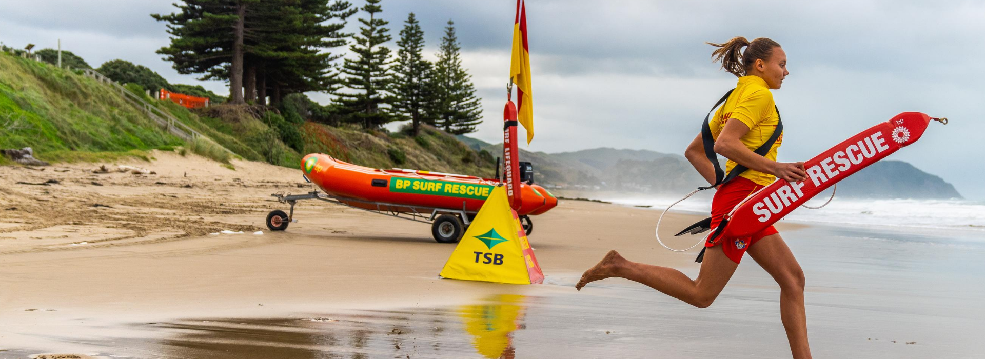 Female Lifeguard Running into Water with Rescue Tube 2