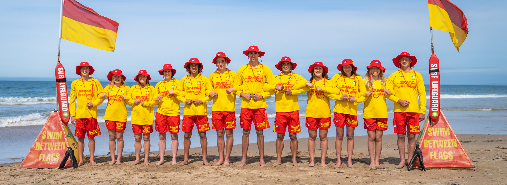 Lifeguards between flags arms together group